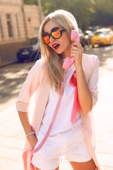 通りを歩いて、かわいい流行の服を着て、若いスタイリッシュな流行に敏感な女性の夏の日当たりの良いライフスタイルファッションの肖像画、