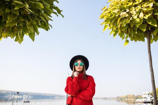 通りを歩く若いスタイリッシュな流行に敏感な女性の夏の日当たりの良いライフスタイルファッションの肖像画
