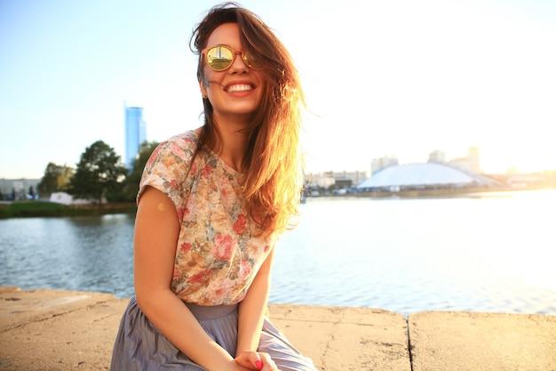젊은 세련 된 hipster 여자의 여름 햇살 라이프 스타일 패션 초상화. 여름에 공원에서 생각하고 옆으로 바라보는 하얀 치아를 가진 여자
