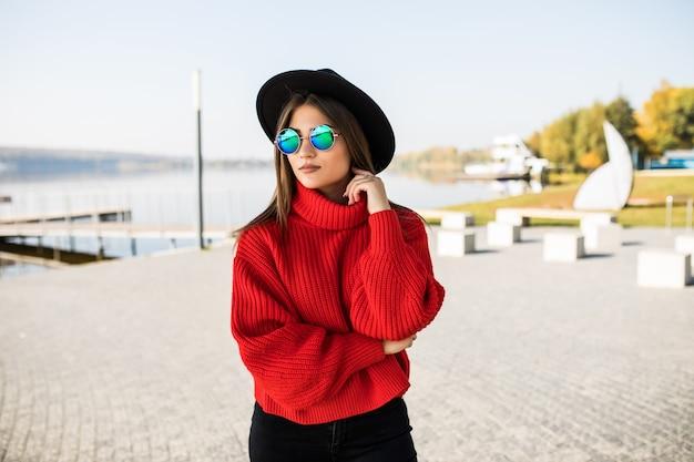 通りを歩いている若いスタイリッシュな流行に敏感な女性の夏の日当たりの良いライフスタイルファッションの肖像画