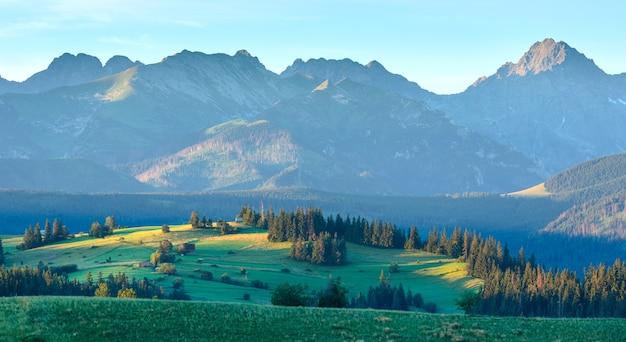 夏の日の出の山の村の郊外の景色とポーランドの背後にあるタトラの範囲