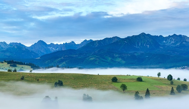 Summer sunrise mountain village outskirts with fog and tatra range  (gliczarow gorny, poland)