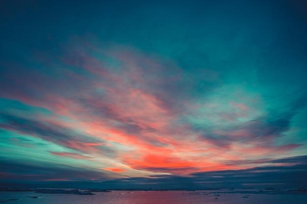 南極の夏の日没。海と氷河の上の劇的なカラフルな曇り空。美しい自然の背景