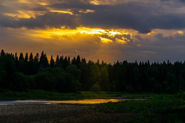 Летний закат над северной рекой с дикими лесными берегами