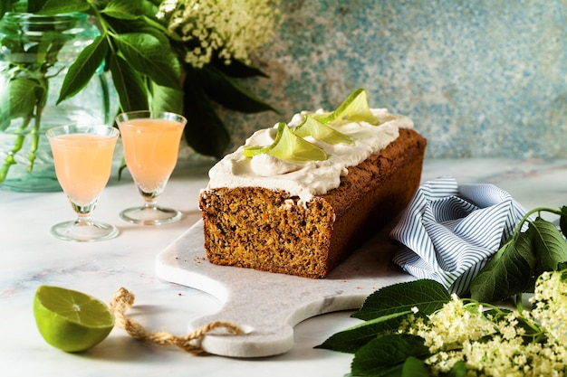 Summer sweet loaf cake on a table with flowers and a drink in glasses. with coconut cream and lime. dessert for brunch or morning breakfast
