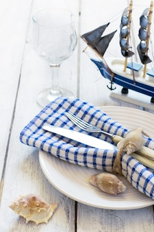 Summer table setting with sea decor on a white boards background