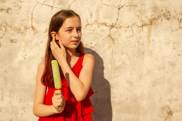 アイスクリームと夏のティーンエイジャーの女の子。緑のアイスクリームと赤いドレスを着た暑い蒸し暑い日の女の子。