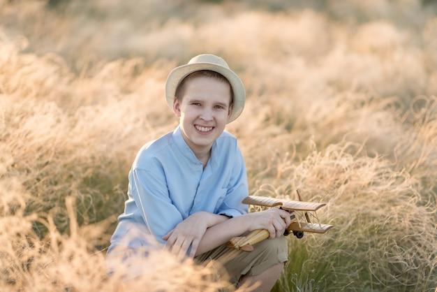 高い草に笑みを浮かべて座っている飛行機モデルと夏のティーンエイジャー。