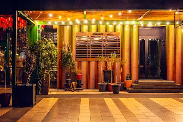 Летняя веранда в кафе вечером, украшенная гирляндами, с растениями в горшках, бочонками на кафельном полу.