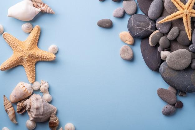 Летняя текстура морская звезда морская ракушка галька вид сверху синий фон
