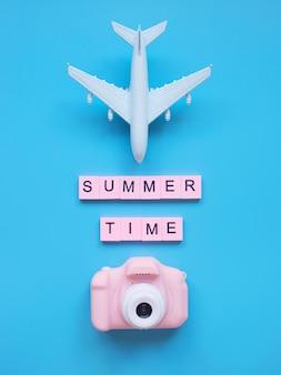 夏時間の背景模型飛行機と青い背景の上のピンクのカメラ