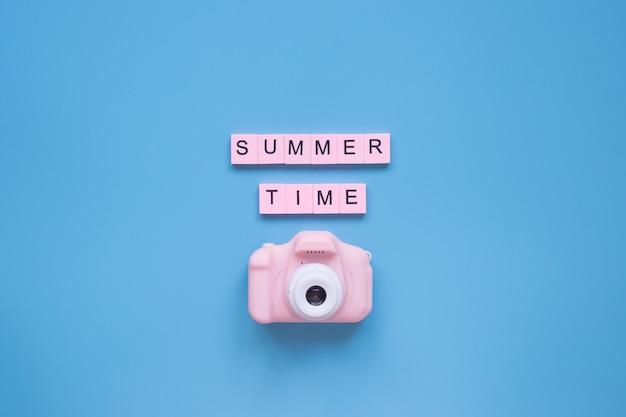 青い背景の夏の背景ピンクのカメラ旅行のコンセプト