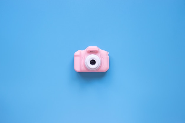 青い背景の旅行のコンセプトに夏時間の背景ピンクのカメラ