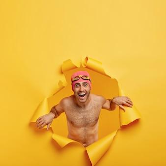 여름 시간 개념. 기쁘게 웃는 남자가 바다에서 이완하고 스파 리조트가 있으며 종이 구멍에 알몸으로 서 있습니다.