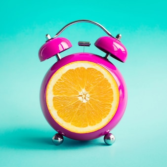 Summer time concepts ideas with orange alarm clock on blue