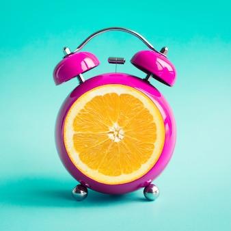 青のオレンジ色の目覚まし時計で夏の時間の概念のアイデア