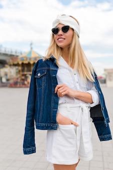 通りの服を着たジャケットと眼鏡をかけた白いスーツの上を歩いている愛らしい女性の大都市での夏の時間。積極性を表現する、カメラに微笑む、楽しい陽気な気分、本当の感情、休暇