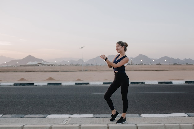 Summer time of joyful young woman in sportswear walking, looking at watch on hand, smiling on road in tropical country. cheerful mood, workout, sunny morning, attractive model.
