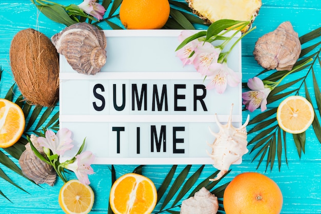 Summer time title on table among plant leaves near fruits with blooms