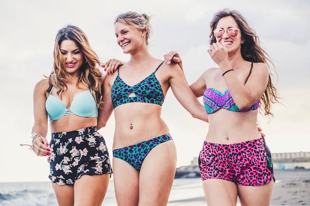 Летние каникулы с тремя молодыми симпатичными женщинами-туристами, гуляющими вместе в бикини в дружбе на берегу на пляже с чистым небом