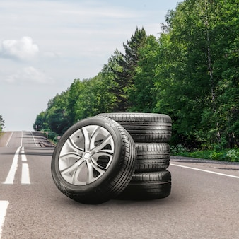 Summer tires and alloy wheels set on an asphalt road. tire change season, auto trade, copy space, square photo. autotuning