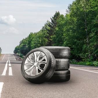 아스팔트 도로에 설치된 여름 타이어와 합금 바퀴. 타이어 교체 시즌, 자동차 무역, 복사 공간, 정사각형 사진. 오토 튜닝