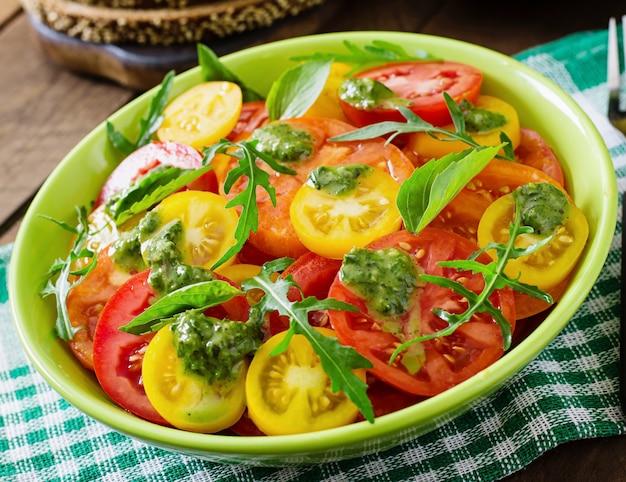 Summer tomato salad with basil, pesto and arugula