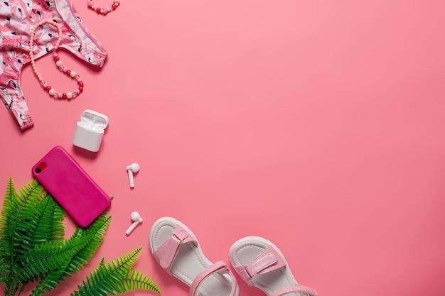 夏のトップビューコンセプトの女の子の水着とサンダル、ピンクの背景にアクセサリーが付いています...