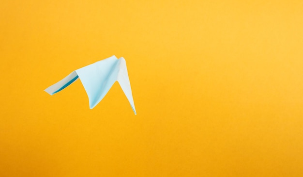 Summer tourism, origami paper airplane on yellow background with copy space.