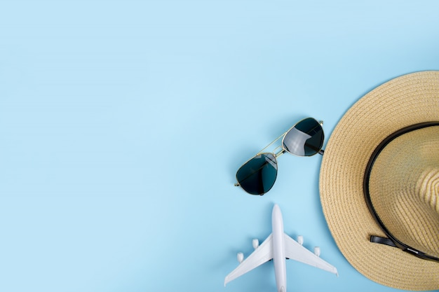 Summer travel accessories and objects on a blue background copy space.