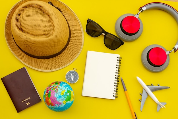 Summer travel accessories and objects on yellow background copy space, for beach vacation journey with plane camera notebook, for travel poster and banner advertisement