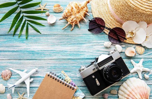 夏の旅行のコンセプト。青い木製の背景に古いフィルムカメラ、帽子、シェル、ヤシの葉。