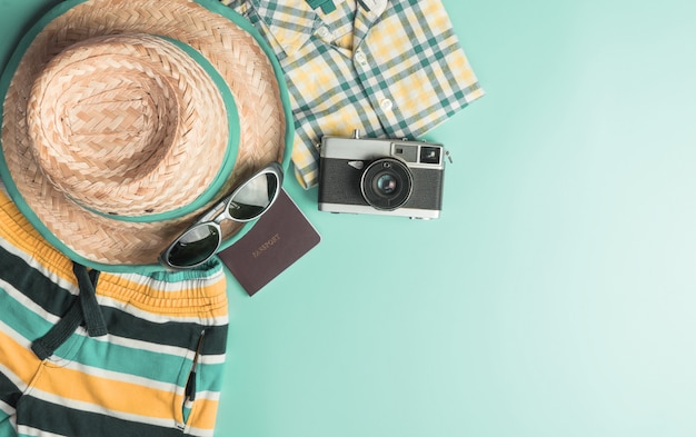 Summer travel fashion and accessories travel top view flatlay on teal pastel