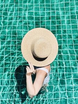 여름 여행 패션과 휴가 개념. 밀짚 모자와 흰색 수영복을 입은 아름다운 젊은, 검게 그을린 여자가 수영장에 서 있습니다.