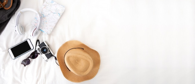 Summer travel items on blanket on bed.top view of accessories travel