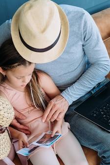 Воспоминания и впечатления о летних путешествиях. папа и его дочь просматривают распечатанные фотографии из отпуска на море