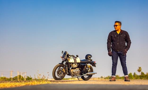 Летнее путешествие на мотоцикле, водитель мотоцикла в черной кожаной куртке стоит на дороге с протянутым старинным мотоциклом, выборочный фокус