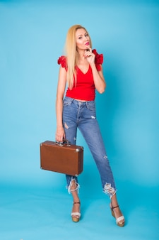 Концепция лета, путешествий, людей и праздников - модная молодая белокурая женщина с ретро чемоданом, изолированным на голубой стене.