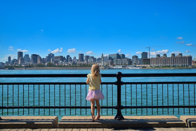 Summer travel tourist little girl enjoying view of old port skyline from montreal park living a happy lifestyle walking during canada vacation.