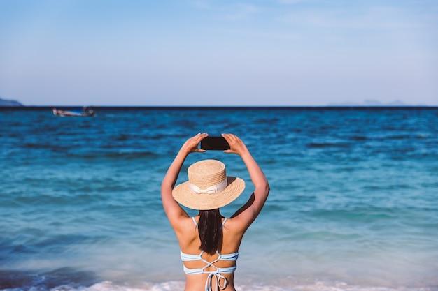 여름 여행 휴가 개념, 태국 사툰 코 리페의 해변에서 휴대전화를 사용하고 휴식을 취하는 행복한 여행자 아시아 여성