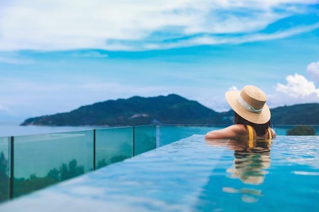 여름 여행 휴가 개념, 모자와 비키니를 입은 행복한 여행자 아시아 여성은 태국 푸켓의 고급 인피니티 풀 호텔 리조트에서 휴식을 취합니다.
