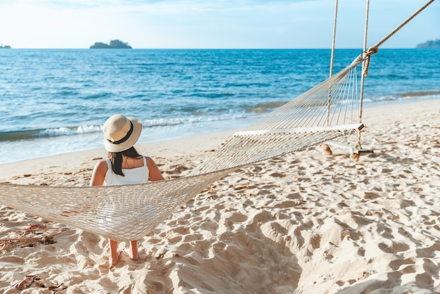 여름 여행 휴가 개념, 모자를 쓴 행복한 여행자 아시아 여성은 태국 트라드 코창 해변의 해먹에서 휴식을 취합니다.