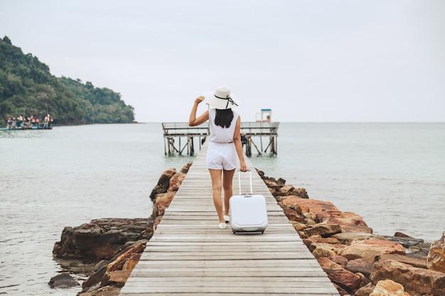 Summer travel vacation concept, happy traveler asian woman with suitcase bag and straw hat walking on wooden bridge in sea beach at koh kood, trad, thailand
