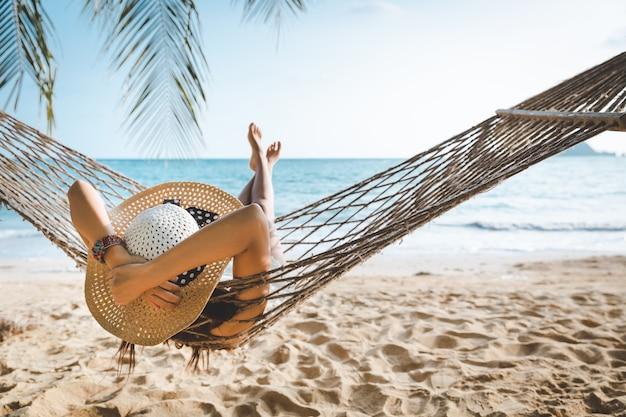 여름 여행 휴가 개념, 흰색 비키니를 입은 행복한 여행자 아시아 여성은 태국 코막 해변의 해먹에서 휴식을 취합니다.