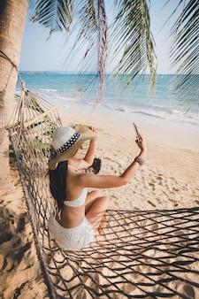 여름 여행 휴가 개념, 흰색 비키니를 입은 행복한 여행자 아시아 여성, 휴대전화를 사용하고 태국 코막 해변의 해먹에서 휴식