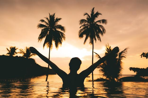 Концепция летних каникул, силуэт азиатской женщины счастливого путешественника расслабиться и поднять руку в пейзажном бассейне на курорте с пляжем на закате в ко куд, таиланд