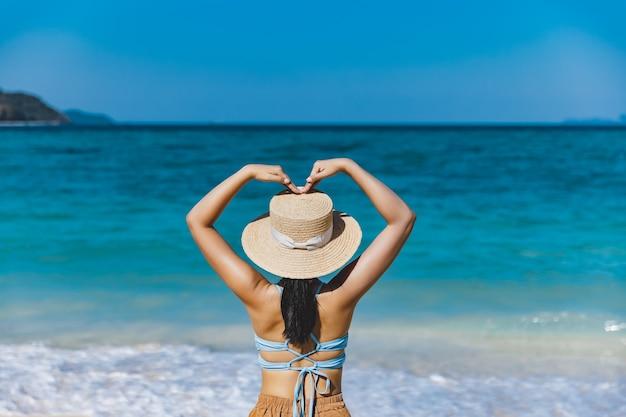 여름 여행 휴가 개념, 비키니와 모자를 쓴 여행자 아시아 여성은 태국 사툰 코 리페에서 하루에 해변에서 심장 모양에 손을 얹고 휴식을 취합니다.