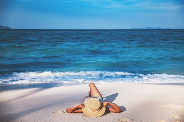 여름 여행 휴가 개념, 비키니와 모자를 쓴 여행자 아시아 여성은 태국 사툰 코 리페에서 하루에 바다 해변에서 휴식을 취합니다.