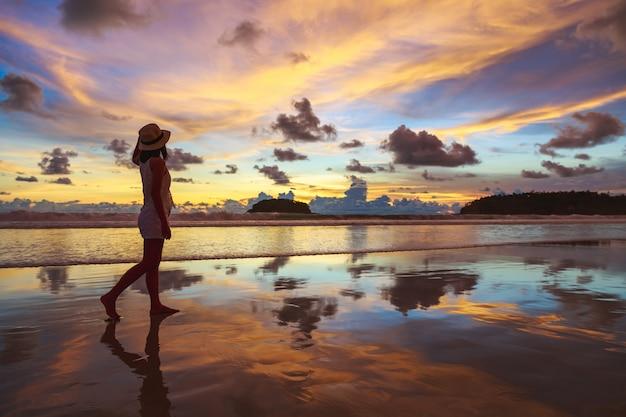 夏の旅行休暇の概念、帽子を持つ旅行者のアジアの女性はリラックスして、タイのプーケットで日没でカタビーチで観光