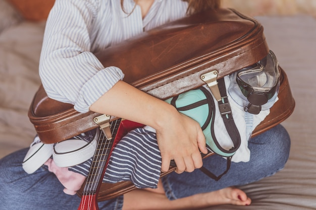 Summer travel and vacation . young woman packing suitcase at home